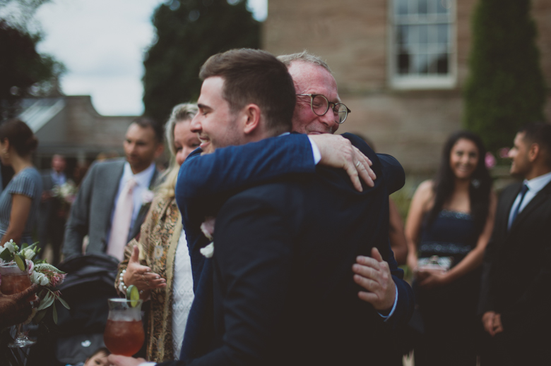 groom hugging dad - Asian Wedding Photography