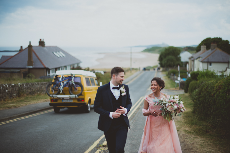 bride and groom walking - Western Asian Wedding Photography - coastal wedding Northumberland coast wedding