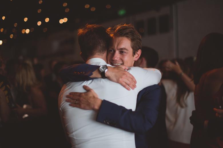 groom and friend hug