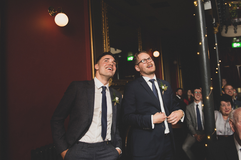 hoxton hall wedding, groom and best man laughing, watching the screen