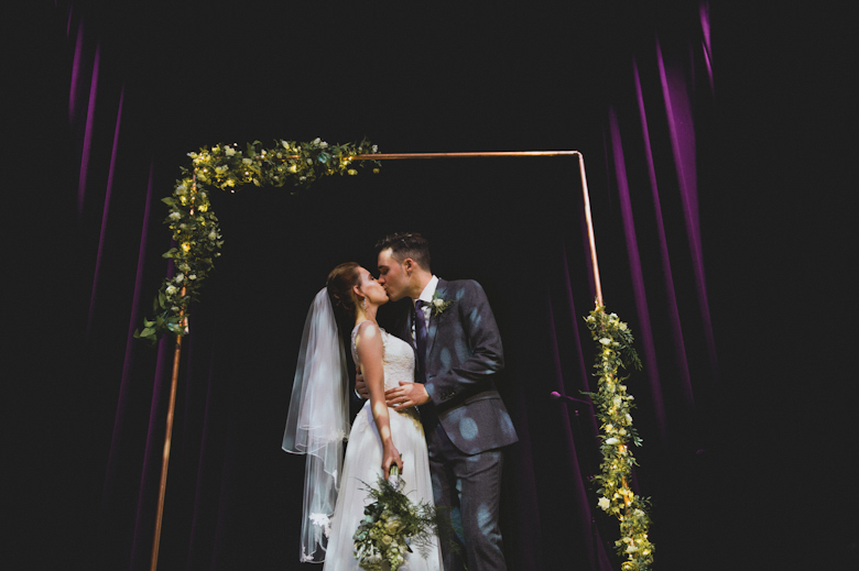 Hoxton Hall wedding London wedding photographer - bride and groom kiss on the stage in the theatre