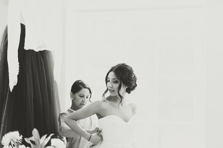 Asylum Chapel Wedding Photographer London - Mum helping bride to put the dress on
