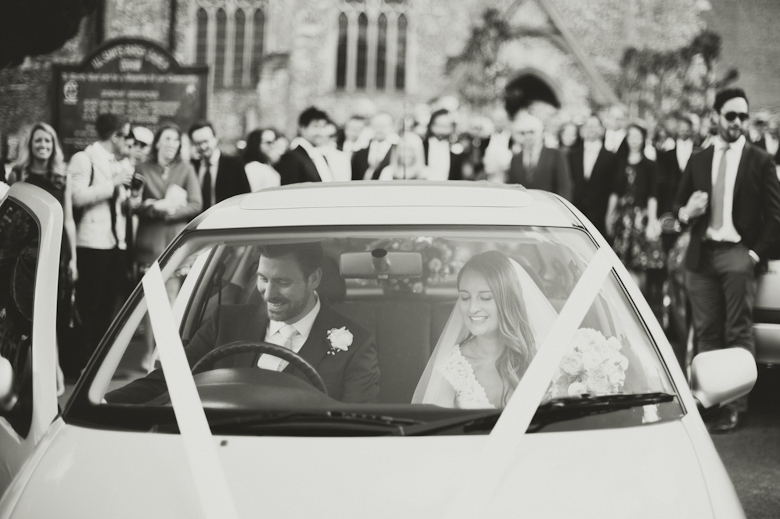 bride and groom getting in the car