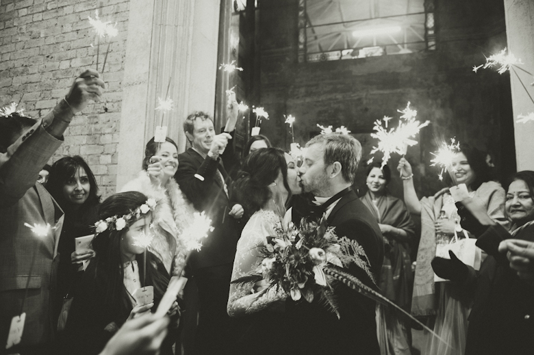 bride and groom kiss and sparklers