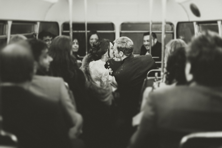 bride and groom kiss on the bus