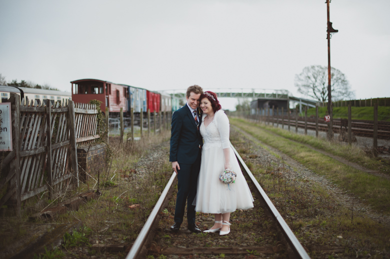 bride and groom on the train tracks
