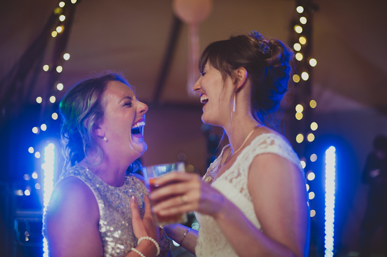 bride and bridesmaid laughing Candid wedding photography
