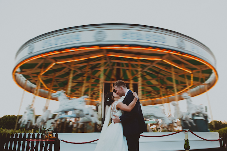 Preston Court Wedding - bride and groom kiss outside the carousel