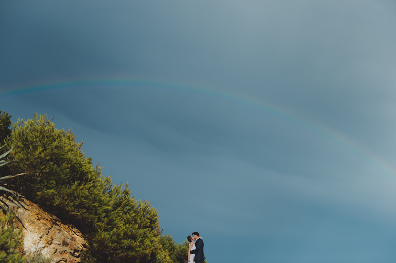 bride and groom with the seaside, rainbow and pine trees