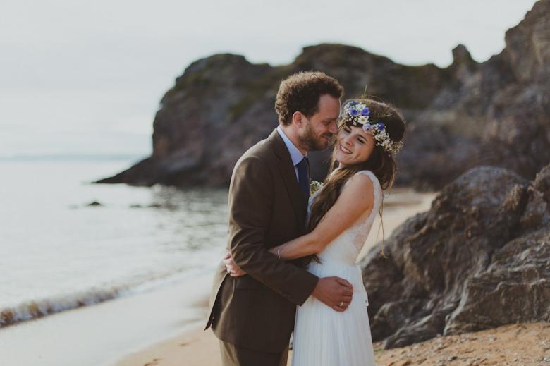 bride and groom on the beach - romantic shot, rocks and beautiful seaside landscape - Fun festival wedding