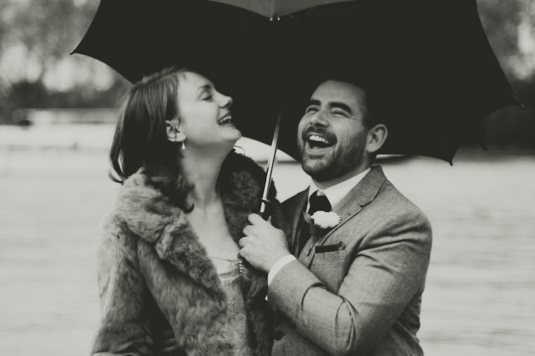 Bride and groom laugh on a rainy wedding day, London