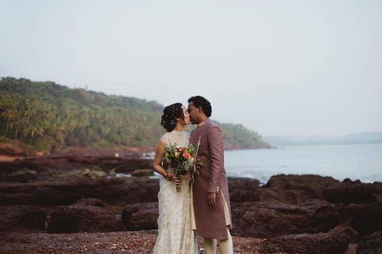 Bride and groom kiss on the Beach, palm trees and seaside, Wedding in Goa by Sasha Weddings - photographer for destination weddings
