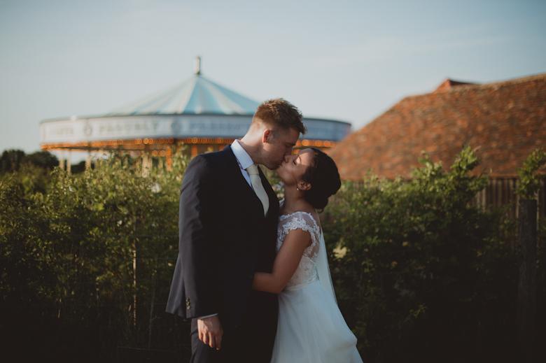 bride and groom kiss outside the carousel at the preston court wedding venue - Sasha Weddings - Kent wedding photographer