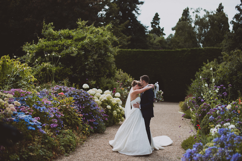 Wedding Photographer Sussex - bride and groom hugging in a garden